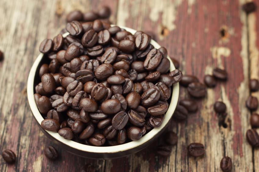 chicchi di caffè tostato in ciotola su tavole di legno