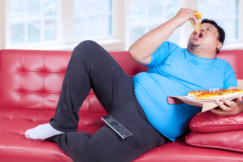 obesità, persona che mangia stesa sul divano