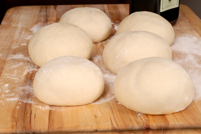 Six balls of freshly made pizza dough on cutting board