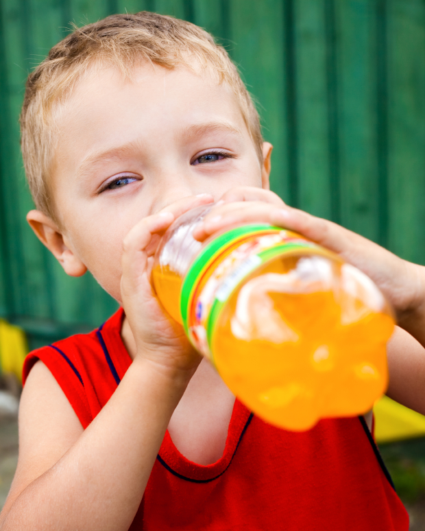 Child drinking unhealthy bottled soda