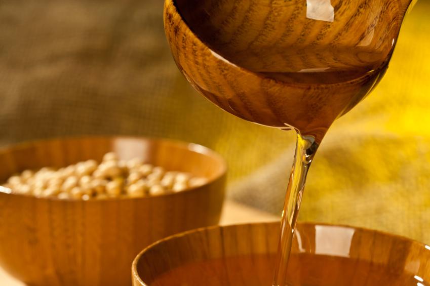 olio di soia versato da mestolo in ciotola di legno semi
