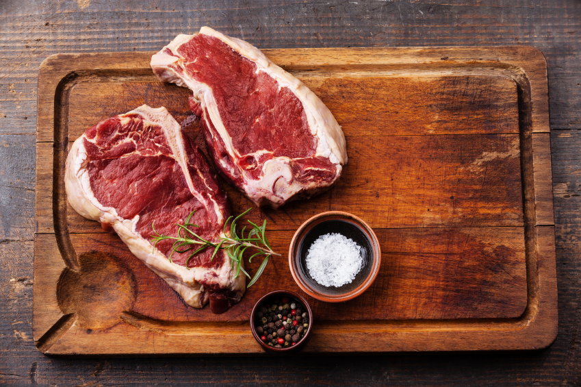 Raw fresh meat Ribeye Steak and seasoning on dark background carne bistecca tagliere sale pepe rosmarino
