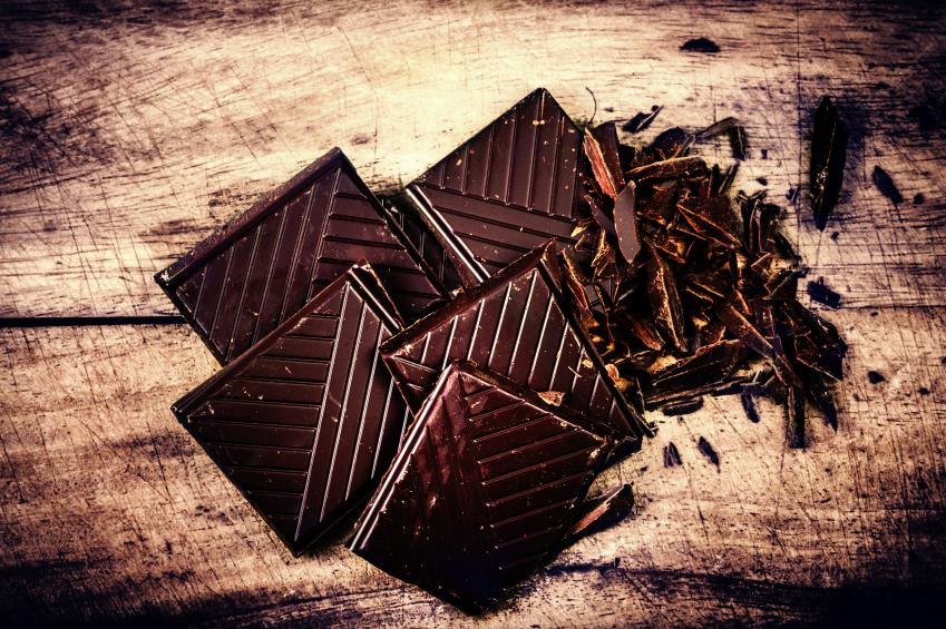 Chopped Chocolate Bar on wooden background closeup. Broken dark chocolate bar on wood table
