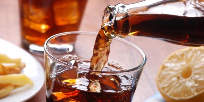 versare bevanda analcolica nel bicchiere di vetro