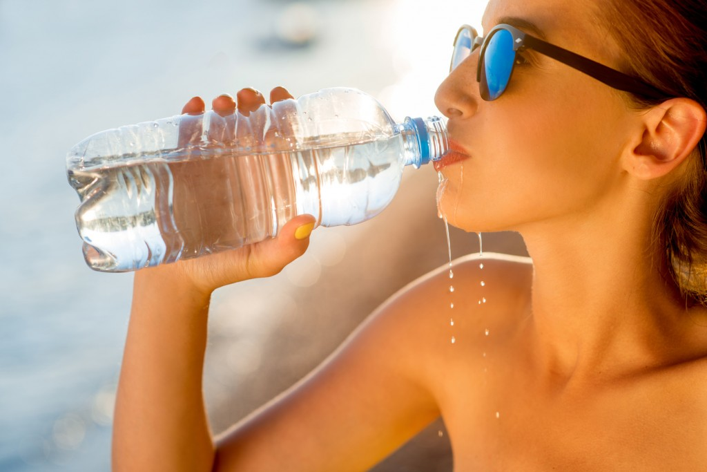 acqua minerale Woman drinking water from transparent bottle on the beach