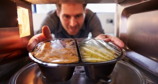 Man Putting TV Dinner Into Microwave Oven To Cook