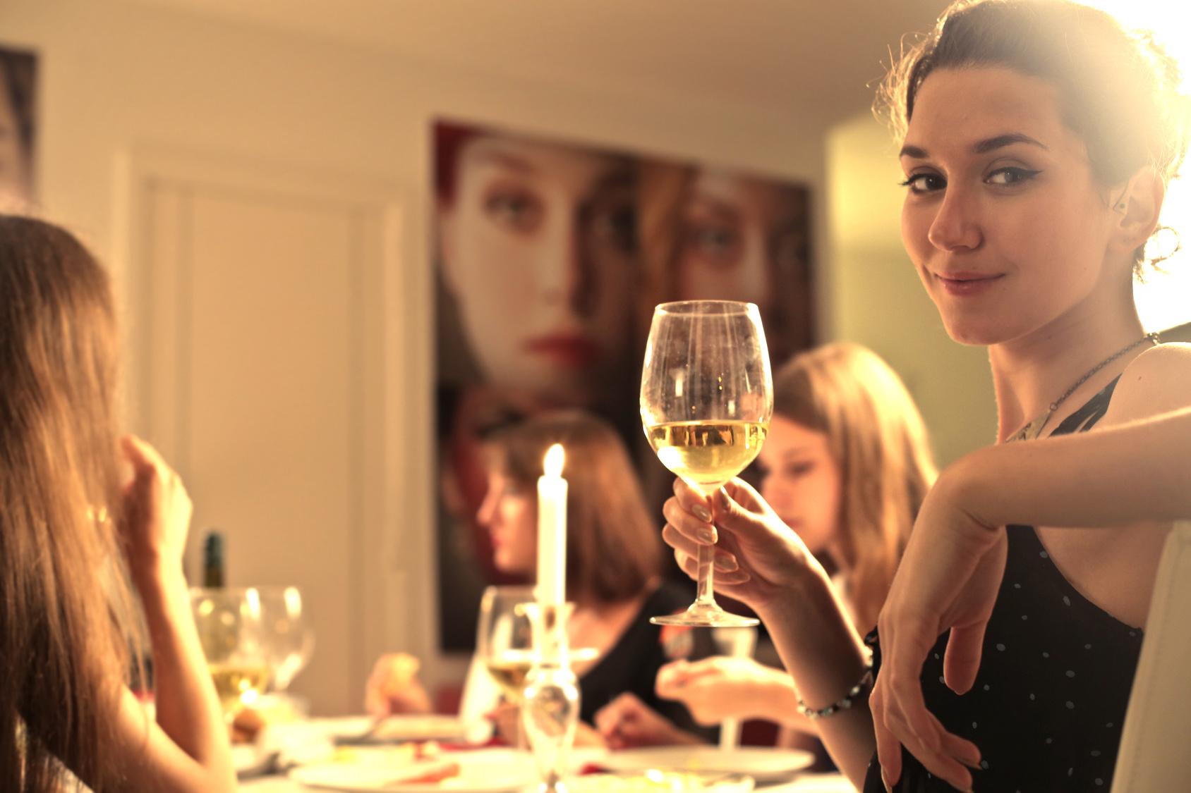 Alcol, donna che beve un bicchiere di vino con dietro una tavola imbandita