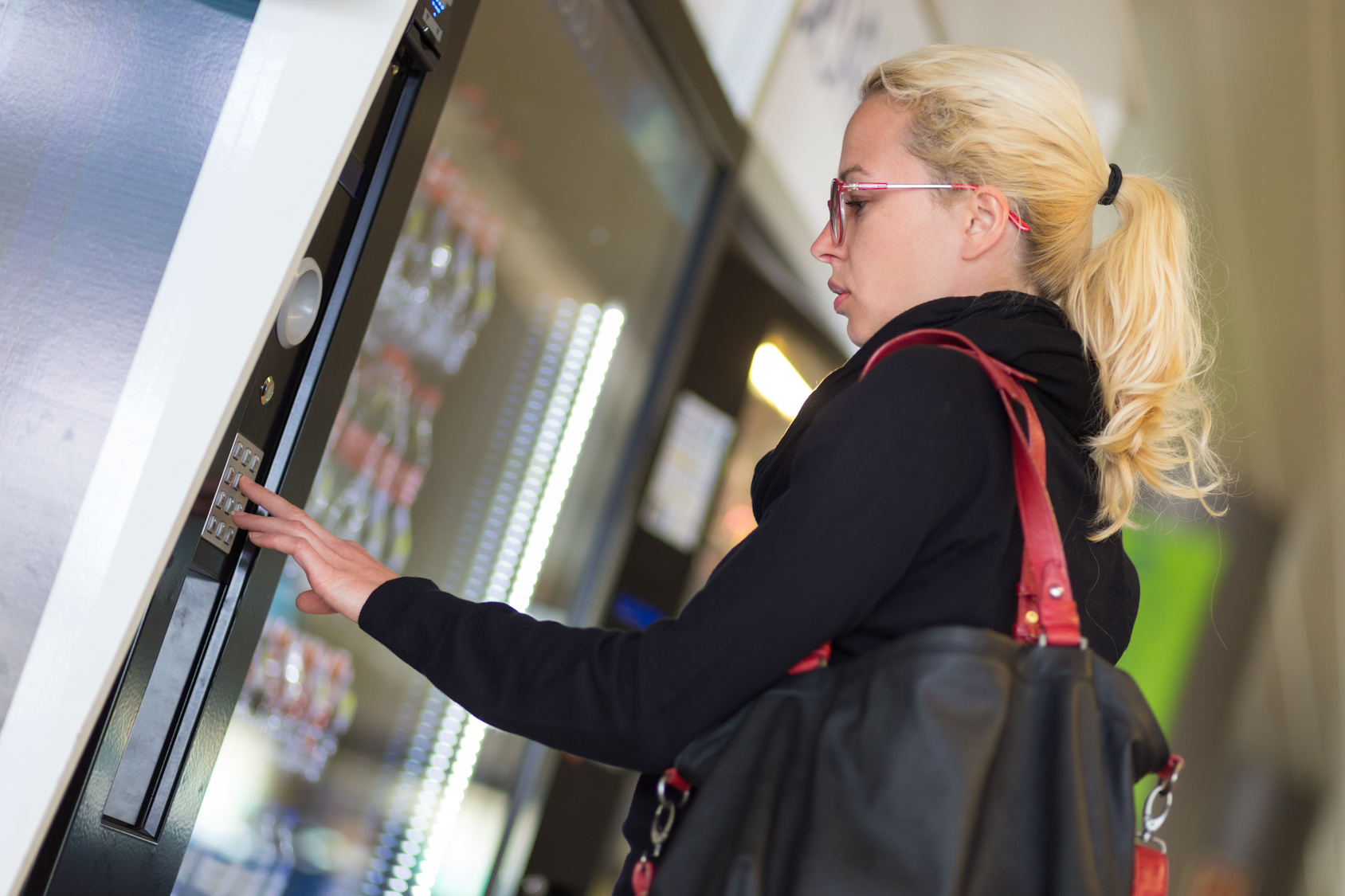ditributori automatici di cibo, ragazza che digita la sua scelta