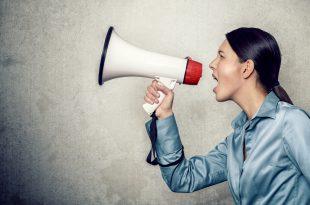 Junge Frau ruft laut mit einem Megafon