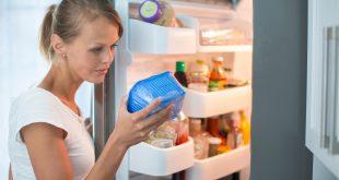 Is this still fine? Pretty, young woman in her kitchen donna controlla data di scadenza etichetta informazioni di conservazione
