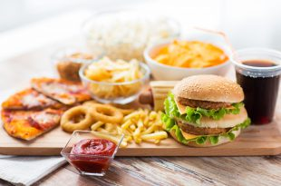 close up of fast food snacks and drink on table alimenti ultra.trasformati