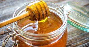 miele che cola in un barattolo di vetro