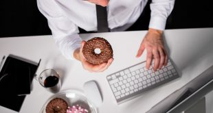 Man at the office eating donuts