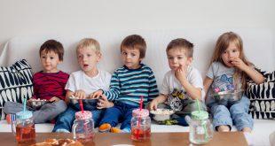 Five sweet kids, friends, sitting in living room, watching TV
