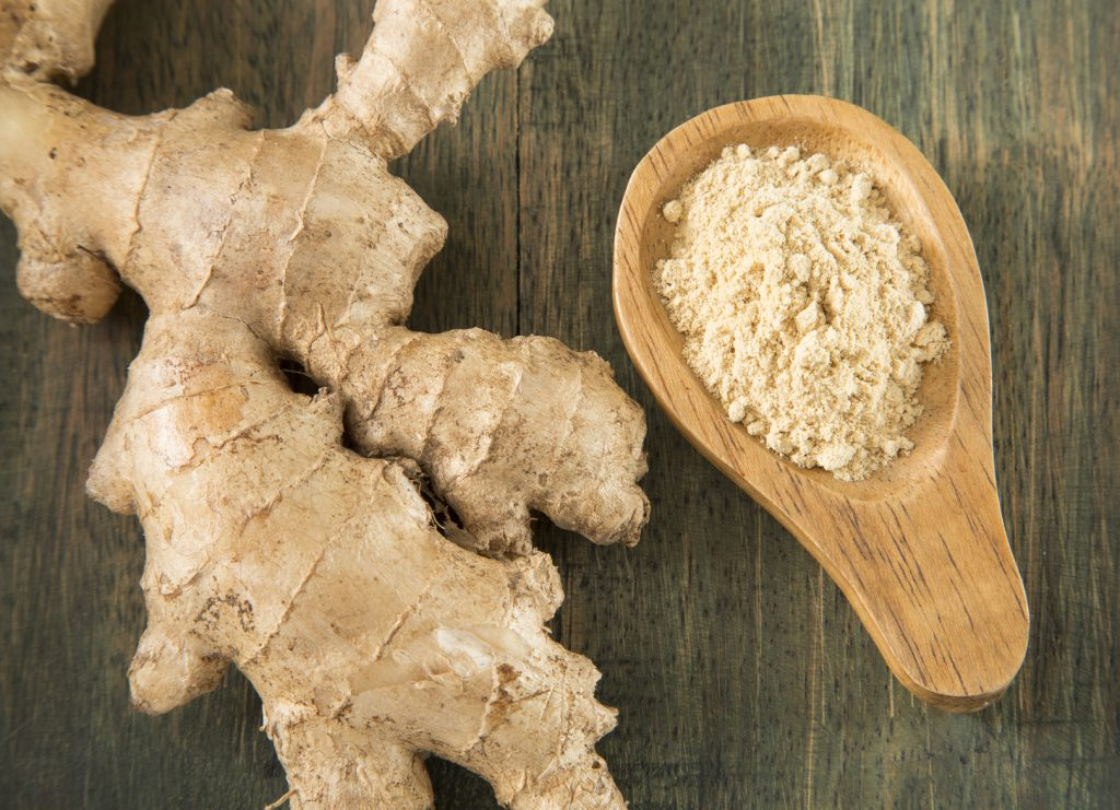 Heap of ginger powder on wooden background