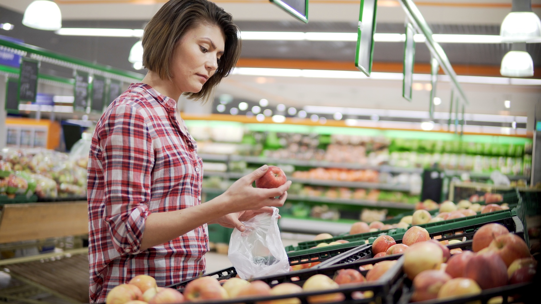 Beautiful woman shopping red apples in supermarket