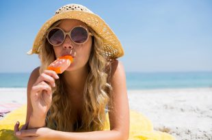 Woman eating popsicle while relaxing at beach