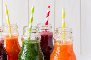 Detox drinks in bottles: fresh smoothies from vegetables: beet, carrot, spinach, cucumber and apple on white background