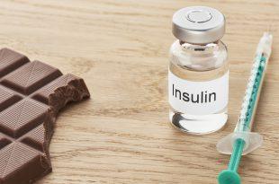 Eine Insulinampulle steht zusammen mit einer Spritze auf einem Tisch daneben liegt ein angebissenes stück Schokolade.