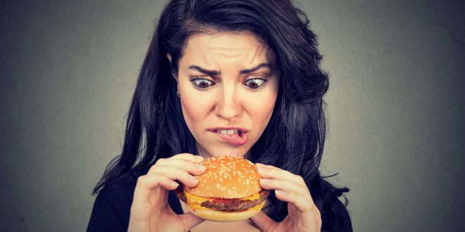 Young woman craving a tasty burger .