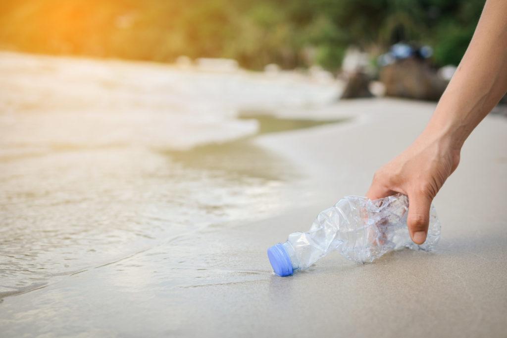 Hand woman picking up plastic bottle cleaning on the beach , volunteer concept spiaggia raccogliere bottiglia di plastica