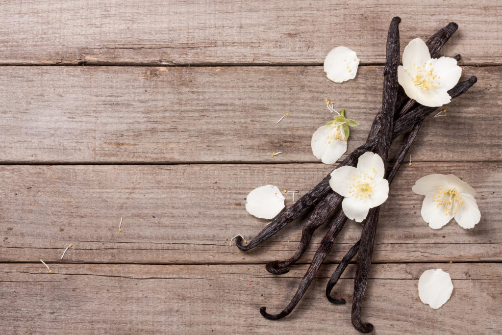 Vanilla sticks with flower and leaf on a old wooden background with copy space for your text. Top view