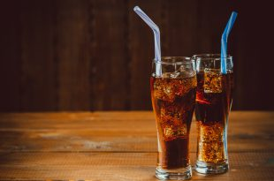 Beautiful cold drink of Cola with ice cubes with a boiler straws in glasses on wooden background with free space