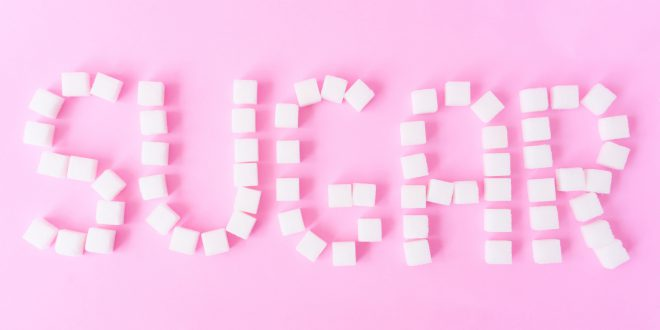 Sugar text with sugar cubes on sweet pink background, food and healthy concept
