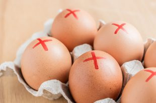 Brown farm eggs with red cross in white carton. Eggs recall over salmonella. How to buy safest eggs after recall