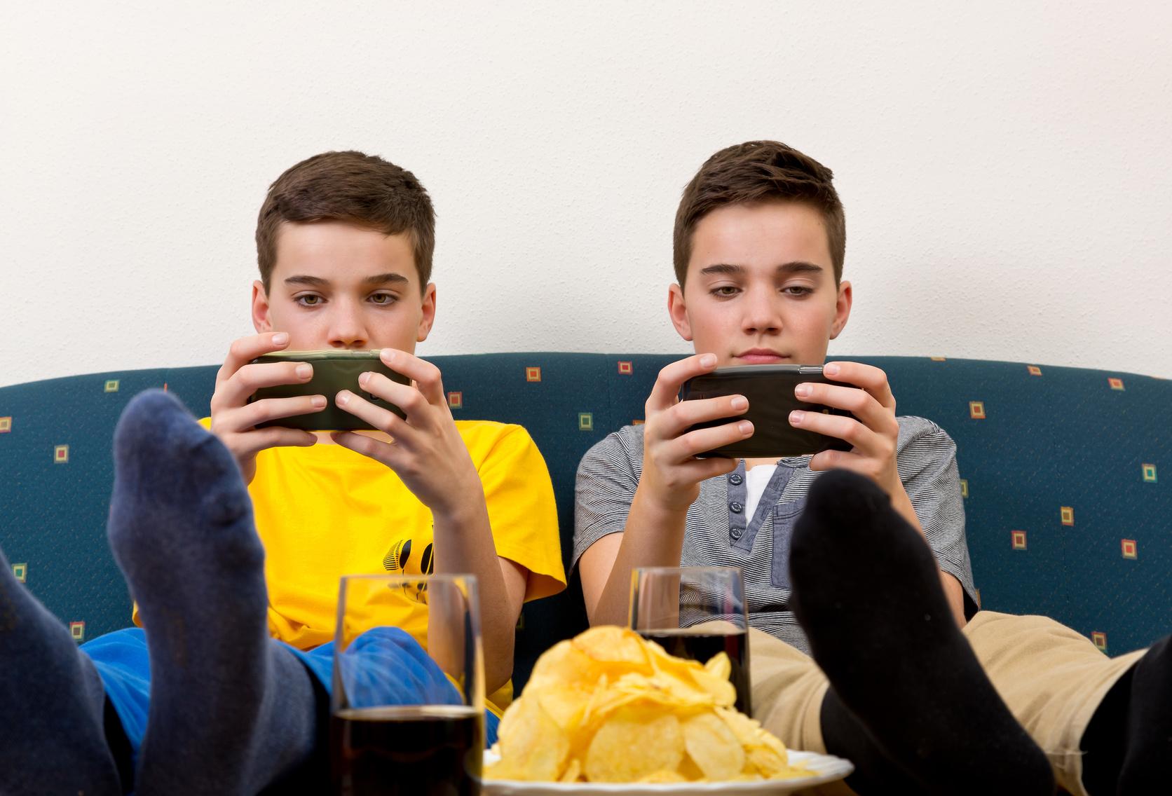 Zwei Jungen mit Smartphone auf der Couch