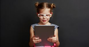 Adorable girl playing game on digital tablet over dark background. Technology and lifestyle.