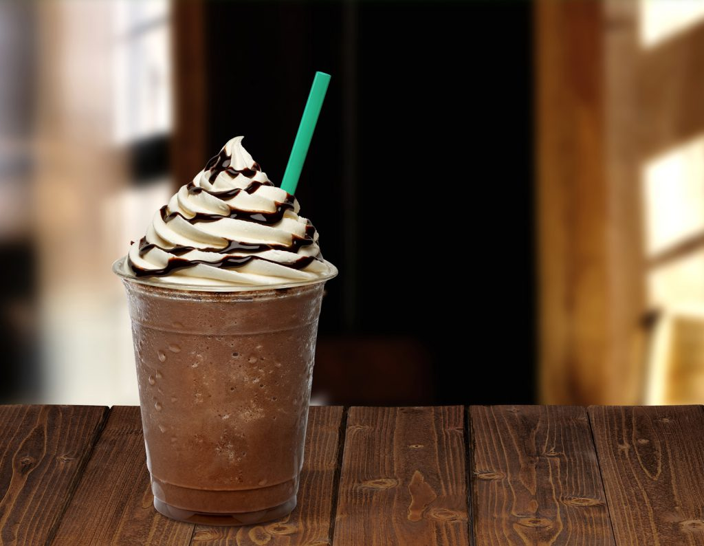 Frappuccino in takeaway cup on wooden table isolated on cafe background