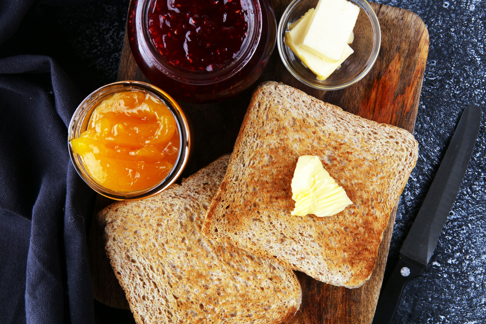 Toast bread with homemade strawberry jam and orange marmalade on rustic table served with butter for breakfast or brunch.
