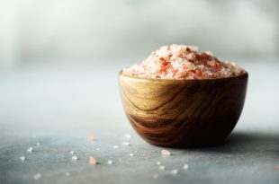 Pink Himalayan salt crystals and powder in wooden bowls on grey concrete background. Healthy diet without salt. Copy space