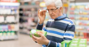 Senior man reading food label at a grocery store