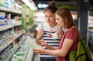 Two pretty female sisters go shopping together, stands in grocer`s shop, select fresh milk in paper container, read label, carry rucksacks, have serious expressions. People and commerce concept