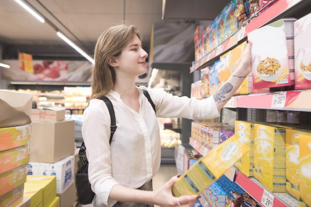 Happy young woman chooses flakes in a supermarket and smiles. A joyful buyer buys products in a supermarket. A girl with packs of quick breakfasts in the hands of the store