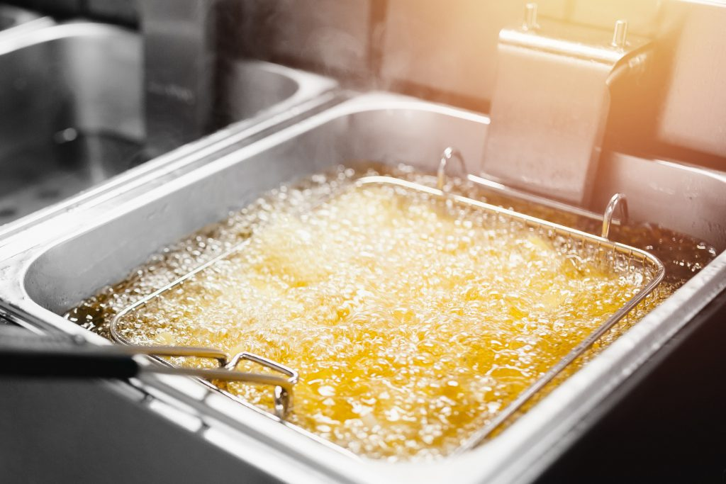 Fryer with French fries, close-up. The oil boils