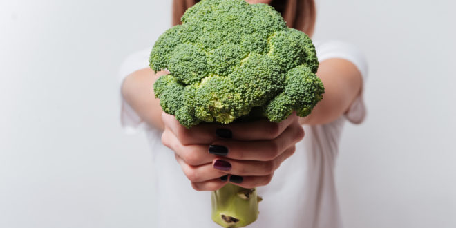 Young woman showing broccoli to camera.