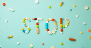 Word STOP from colored pills and capsules on green background. Medicines and tablets kill