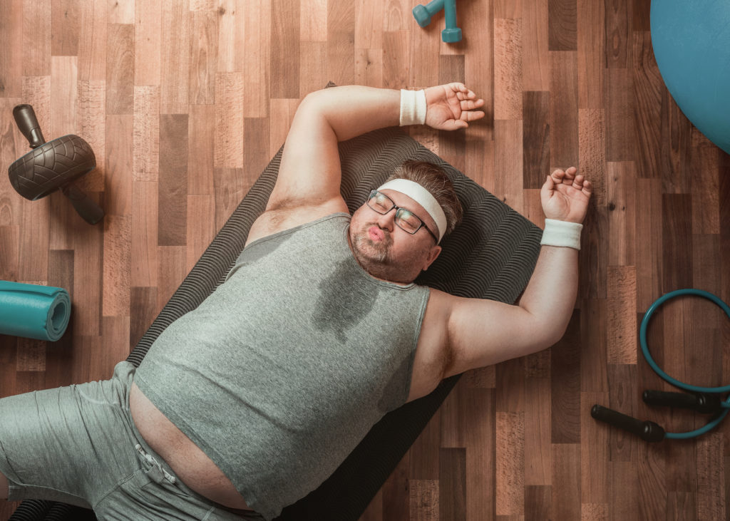 Funny overweight sportsman lying down exhausted on the gym's floor