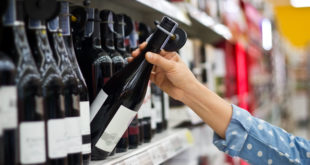 Woman is buying a bottle of wine in supermarket background
