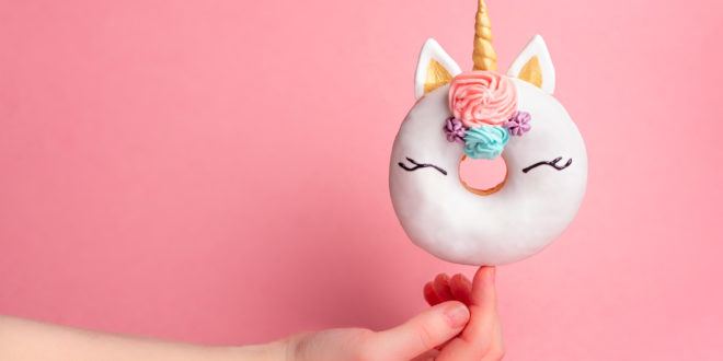 Unicorn donut on forefinger, copy space