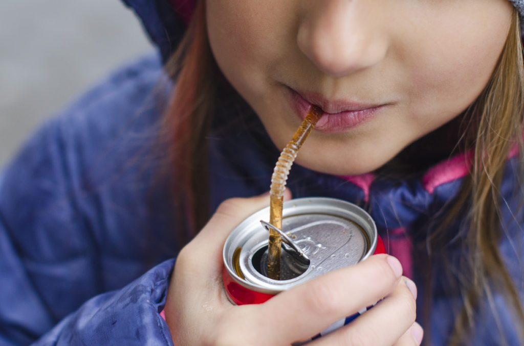 girl drinking a drink through a straw from a can