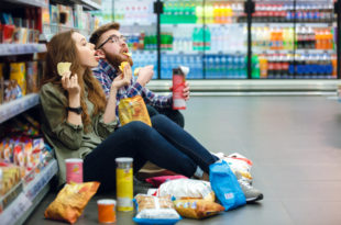 Couple sitting on the supermarket floor and eating snacks