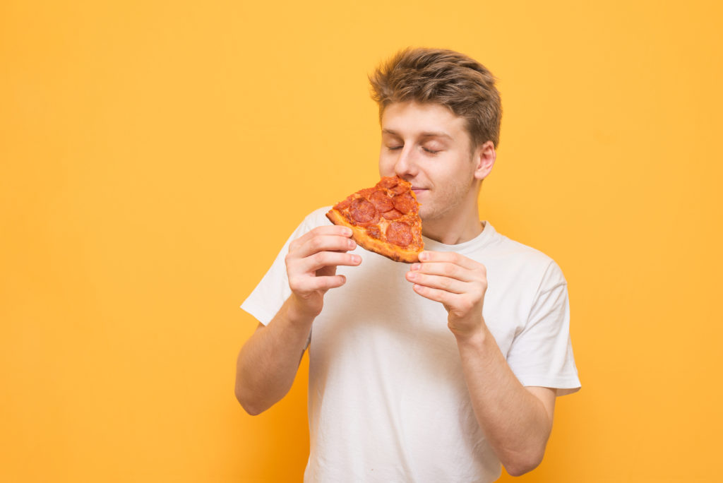 Young man holds a piece of fresh pizza in his hands to smell a scent with his eyes closed, isolated on a yellow background. Guy enjoys fast food on a yellow background.