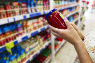 Glass jar of sauce in the hands of the buyer. Sauce in the hands of the buyer at the grocery store