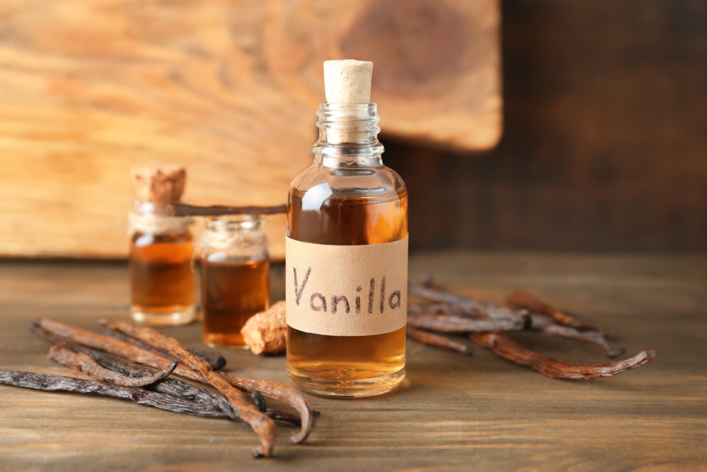 Glass bottle with vanilla extract on wooden table