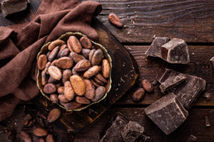 Cocoa beans and chocolate on wooden background