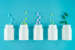 Medicines, supplements and drugs in a bottle on blue background